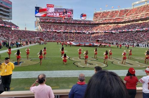 Woman in red and white cheerleader uniform kneeling while flanked by other  women in similar uniforms 4cef37ab7