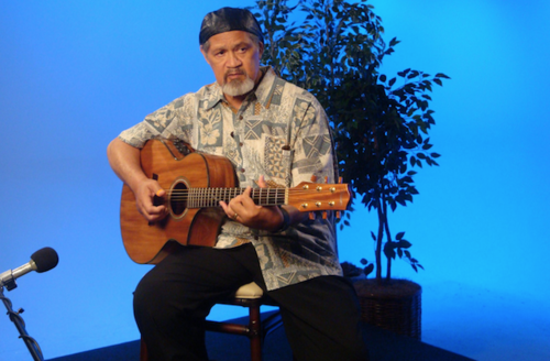 Cyril Pahinui. Brown man in black hat and light green shirt and black pants plays brown guitar in front of blue screen and plant in black shadow