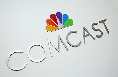 """Silver letters spell """"COMCAST"""" under multicolored NBC logo on off-white background"""