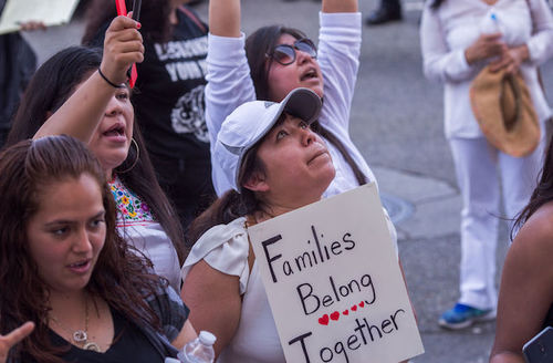 Protestors surround woman holding sign that reads families belong together in protest of the Trump administration's zero tolerance policy immigration and refugee policies in Los Angeles, California on June 30, 2018.
