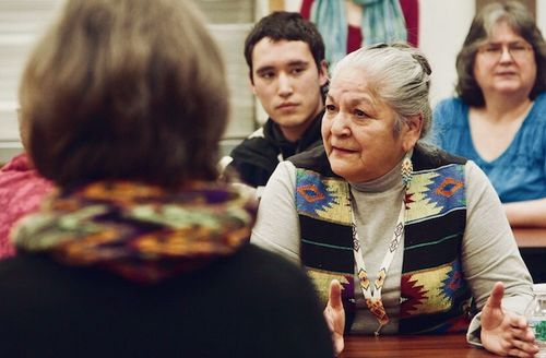 Georginia Sappier-Richardson. Indigenous woman in gray shirt and black and yellow and blue patterned vest speaks at brown wood table in front of Indigenous boy and woman with woman in black shirt and orange and green scarf in foreground