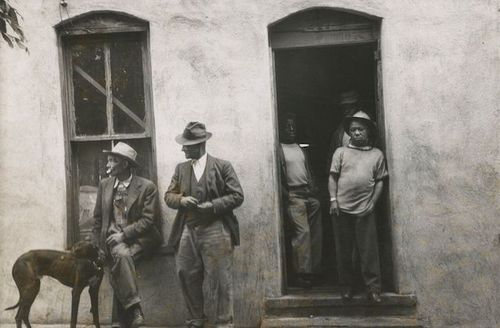 Black-and-white image of Black men and dog in entrance of and outside of pool hall with white wall