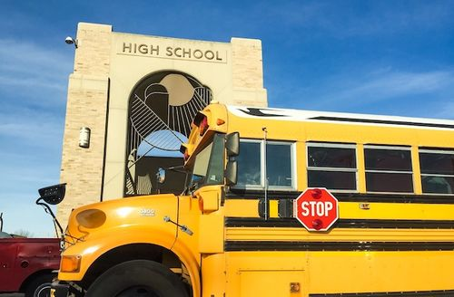 Large school bus in front of a high school.