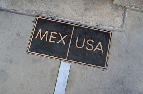 """Black and gold marker on ground reads """"Mex"""" and """"USA."""""""