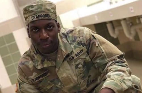 """Emantic Bradford Jr. Black man in green and brown army fatigues and hat with black text reading """"U.S. ARMY"""" poses in front of white sink and white and green tiles"""