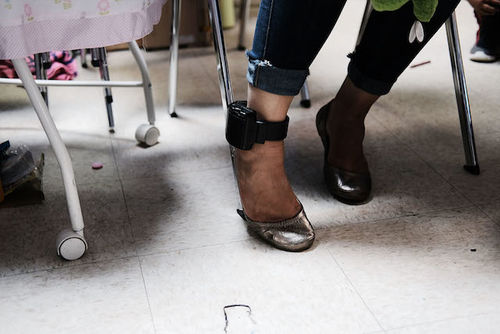 A brown woman wearing metallic gold heels shows her electronic monitoring bracelet.