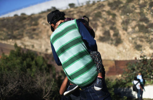 A migrant wearing a green and black shirt carries a child as he approaches the U.S.-Mexico border fence in Tijuana, Mexico on December 16, 2018.