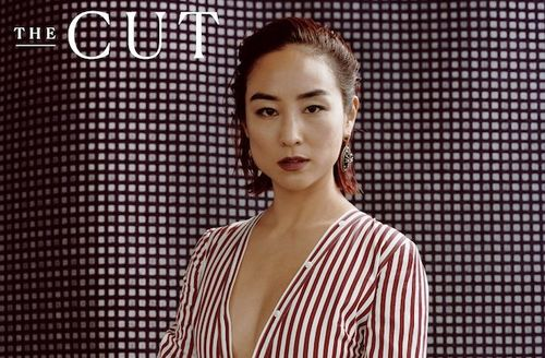 "Greta Lee. Asian-American woman with magenta hair in red and white dress poses in front of grey grid wall and next to white text that reads ""THE CUT"""