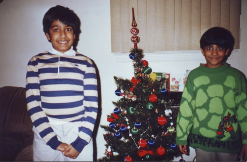 Hari and Ashok Kondabolu. South Asian boy in shirt with navy and white stripes and white pants stands next to South Asian boy with green sweater in front of green Christmas tree with red and green ornaments and white wall and brown window shade