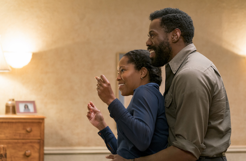 """Regina King and Colman Domingo in """"If Beale Street Could Talk."""" Black woman in blue shirt and Black man in gray shirt dance in front of beige wall"""