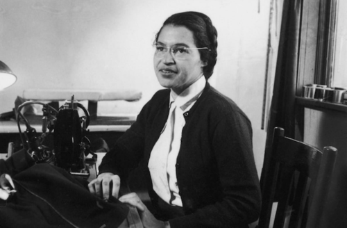 Rosa Parks. Black-and-white photograph of Black woman in black blazer and white shirt at desk and in front of office furniture and curtain