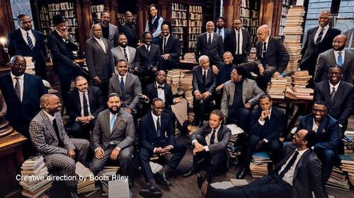 32 Black men in navy and grey and black suits sit or stand around brown bookshelves and furniture