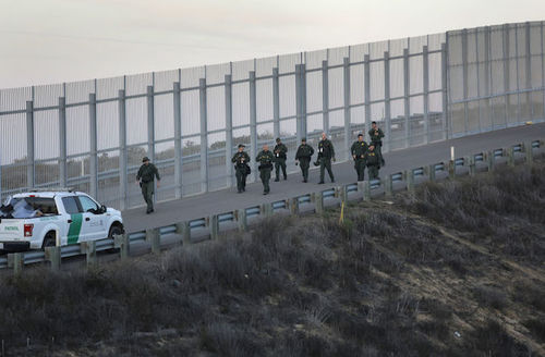 U.S. Border Patrol agents walk back to their vehicles after taking immigrants into custody after they climbed over the U.S.-Mexico border fence from Tijuana, Mexico on December 2, 2018.