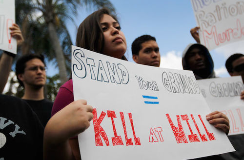 """Grace Miranda, a young Latinx, holds a sign that reads """"Stand Your Ground equals Kill At Will"""" at a rally in the daytime with four other protestors behind her holding signs."""