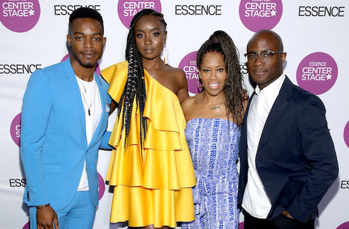 Stephan James, KiKi Layne, Regina King and Barry Jenkins. Black man in light blue suit stands next to Black woman in yellow dress next to Black woman in blue and white romper next to Black man in navy and black suit in front of white wall with purple
