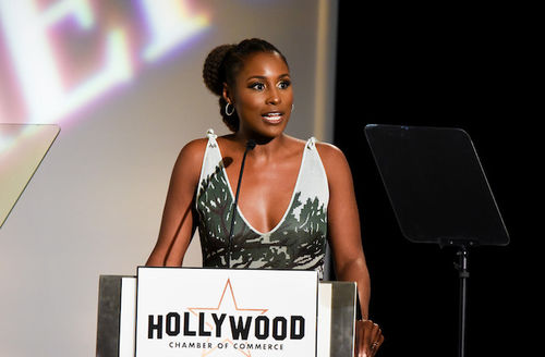 """Issa Rae. Black woman in green and grey dress speaks into black microphone on stand with white sign and back text reading """"HOLLYWOOD CHAMBER OF COMMERCE"""" in front of black microphone and background with white text on screen"""