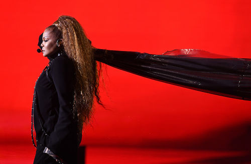 Janet Jackson. Black woman with brown hair wears black outfit and carries black cape in front of red lights