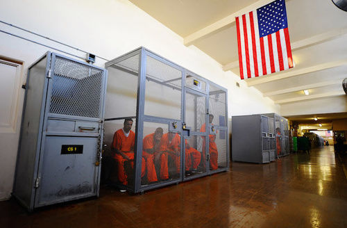 Five incarcerated people in orange jumpsuits are locked in a cell. There is an American flag hanging above the cell.
