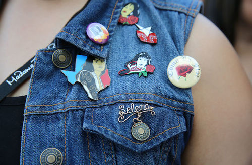 """Multicolored pins, including gold one spelling """"Selena"""" and yellow one with text spelling """"COMO LA FLOR"""" on denim vest worn by person in black tank top in front of crowd"""