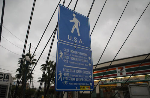 A blue sign points to the pedestrian crossing to the U.S. near the U.S./Mexico border.