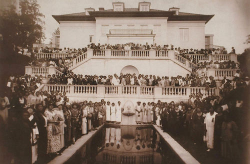 Madam C.J. Walker. Sepia-toned archival photograph of Black people in formal attire on grounds and steps of white mansion