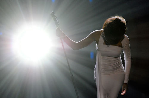 A think Black woman wearing a fitted white gown performs on stage