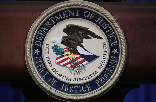 """Brushed gold circle seal with """"Department of Justice Office of Justice Programs"""" written on it in gold on a navy background."""