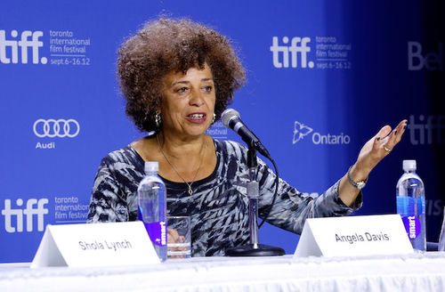 "Angela Davis. Black woman with brown afro sits in blue patterned shirt behind white table with white nametag spelling ""Angela Davis"" in black letters and in front of blue screen with grey letters spelling ""tiff"""
