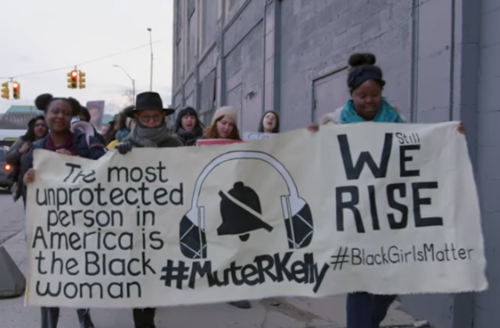 """Black women march in multicolored coats and clothes while holding tan banner with black text reading """"WE RISE"""" and """"The most unprotected person in America is the Black woman"""" and """"#MuteRKelly"""" in front of grey building and sky."""