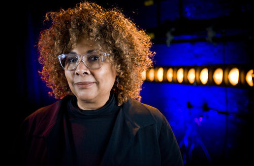 Julie Dash. Black woman with blonde curly hair poses in clear eyeglasses and black shirt in front of blue and yellow lights