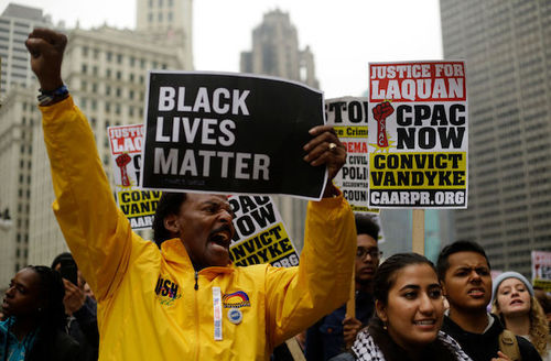 """Black man in yellow jacket with fist up, holding black and white sign that reads, """"Black lives matter."""" Crowd surrounds him."""