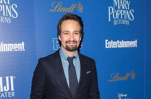 """Lin-Manuel Miranda. Latinx man with black hair and beard in dark suit with blue tie and shirt in front of blue wall with light blue text spelling """"MARY POPPINS RETURNS"""" and white text spelling """"Entertainment"""""""