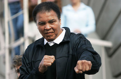 Muhammad Ali. Black man with black hair poses in fighter's stance in black jacket and sweater and white shirt in front of beige ladder and wall and bannister