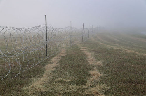 Razor wire stretches out in the morning fog near the U.S.-Mexico border in Donna, Texas, on November 5, 2018 .