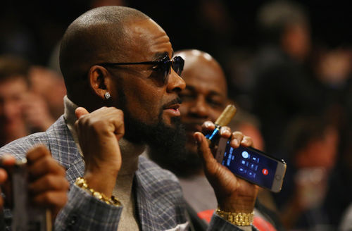 Black man in black sunglasses and grey patterned sports coat and brown shirt and gold jewelry holds black cell phone and brown cigar in front of Black man in grey shirt and blurry audience and black background