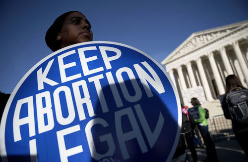 """Black pesron holds blue and white sign the reads, """"Keep abortion legal."""""""