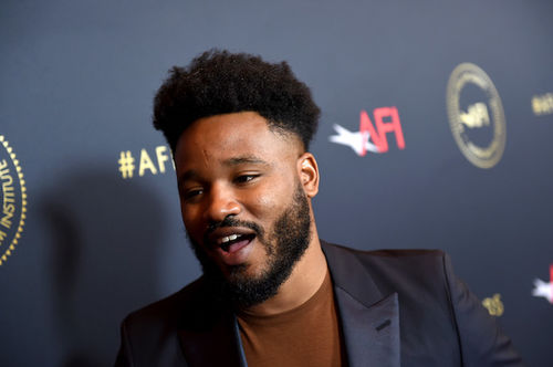 "Ryan Coogler. Black man with black hair and beard smiles in black blazer and orange shirt in front of grey wall with gold and red text spelling ""AFI"""