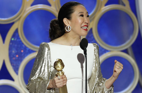 Sandra Oh. Asian woman in black hair and white and gold dress holds gold award statue and smiles in front of blue and gold background