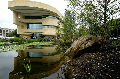 Brown museum building with multiple elliptical layers and glass windows stands behind reflecting pool and green and brown trees and brown soil in front of gray sky
