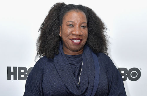 """Tarana Burke. Black woman with black hair smiles in navy sweater in front of white wall with black text that reads """"HBO"""""""