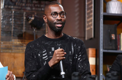 Tarell Alvin McCraney. Black man in black sweater and glasses speaks into black microphone in front of brown wood and walls