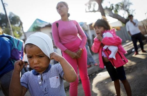 Honduran children stand with their mother outside a temporary shelter set up near the U.S.-Mexico border in Tijuana, Mexico, on November 20, 2018.