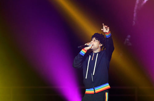 21 Savage. Black man with black dredlocs holds fist in air while wearing navy hoodie with white drawstrings and rainbow accents in front of purple and orange lights.