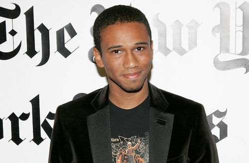 "Aaron McGruder. Black man smiles in black blazer and t-shirt with multicolored logo in front of white wall with black text that spells ""The New York Times"""