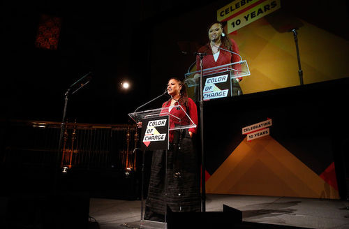 """Ava DuVernay. Black woman with black locs in red blouse and black skirt speaks behind glass podium with black sign with red and yellow panels and black text that spells """"COLOR OF CHANGE"""" and video screen."""