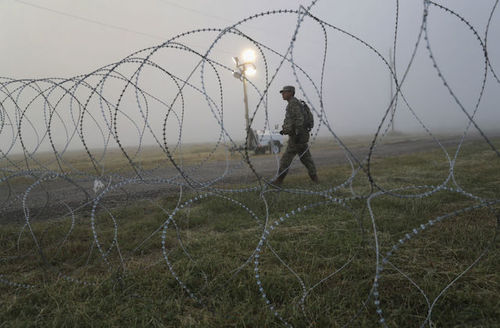 A lone U.S. army soldier patrols the area behind barbed wire near the U.S.-Mexico border in Donna, Texas on November 5,2018.