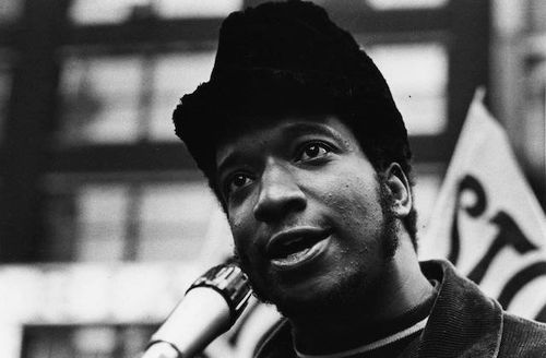 Fred Hampton. Black-and-white photograph of Black man in black hat and jacket in front of white flag with black text and black and white building.