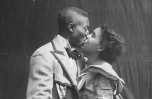 Black-and-white image of Black woman in dress kissing Black man in overcoat in front of curtain.