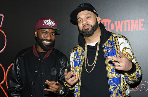 Desus Nice and The Kid Mero. Black man in maroon hat and black and maroon jacket stands next to Brown man in black hat and shirt and white and gold and blue jacket in front of black wall with red Showtime logo.