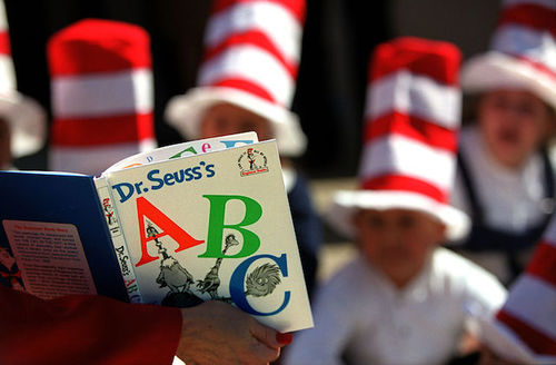 """Person in red top holds white, red, blue and green copy of """"Dr. Seuss's ABC"""" while children in red and white striped hats sit and listen in background"""